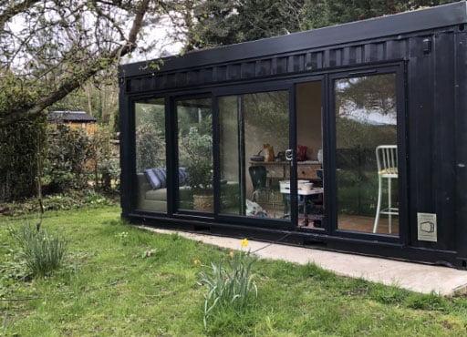 Dark shipping container office in garden