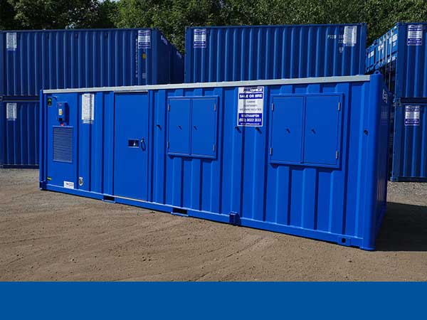 A single blue welfare unit in front of blue containers stacked