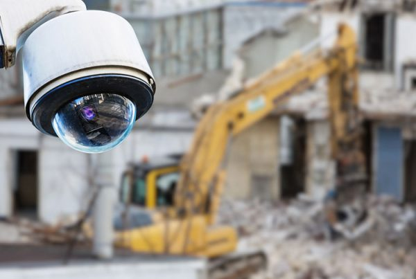 A CCTV camera in the top left corner of the image in the foreground, with a blurred construction equipment in the background