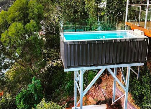 A raised shipping container balcony pool on stilts surrounded by trees
