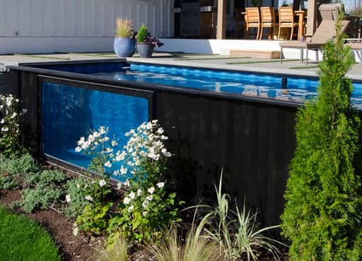 A converted shipping container pool with viewing port built into a garden patio in glorious sunshine
