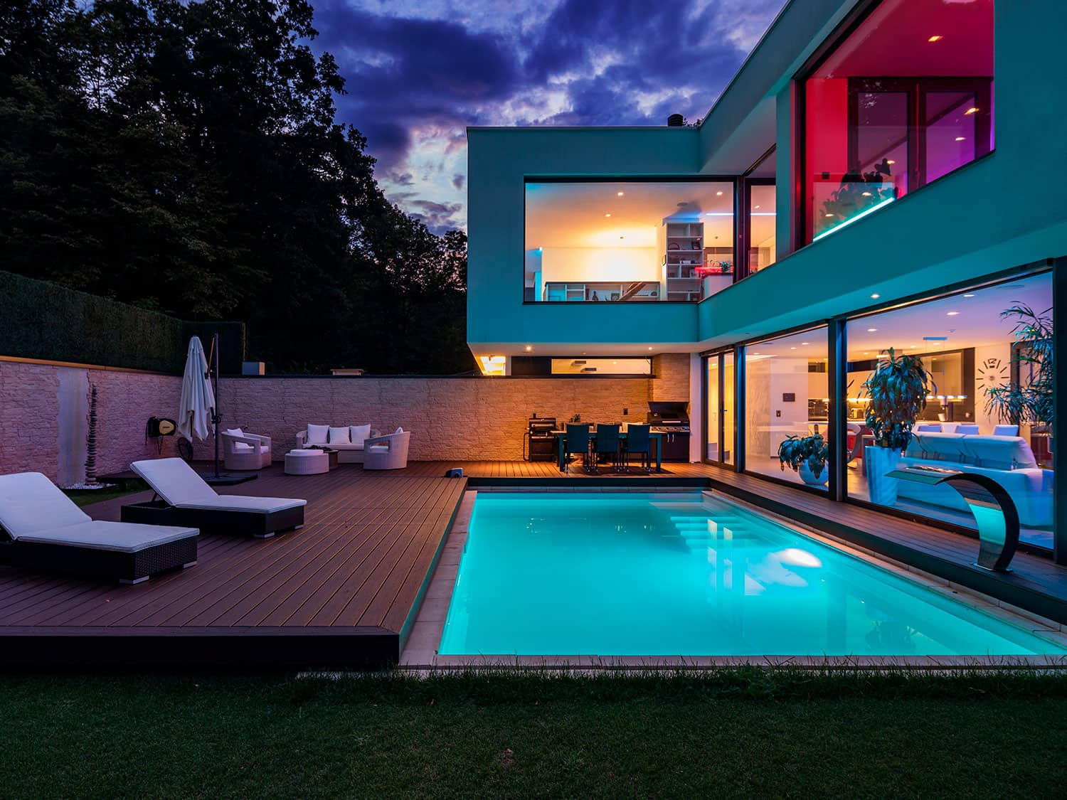 A ground-based shipping container swimming pool set against the backdrop of a container home at night