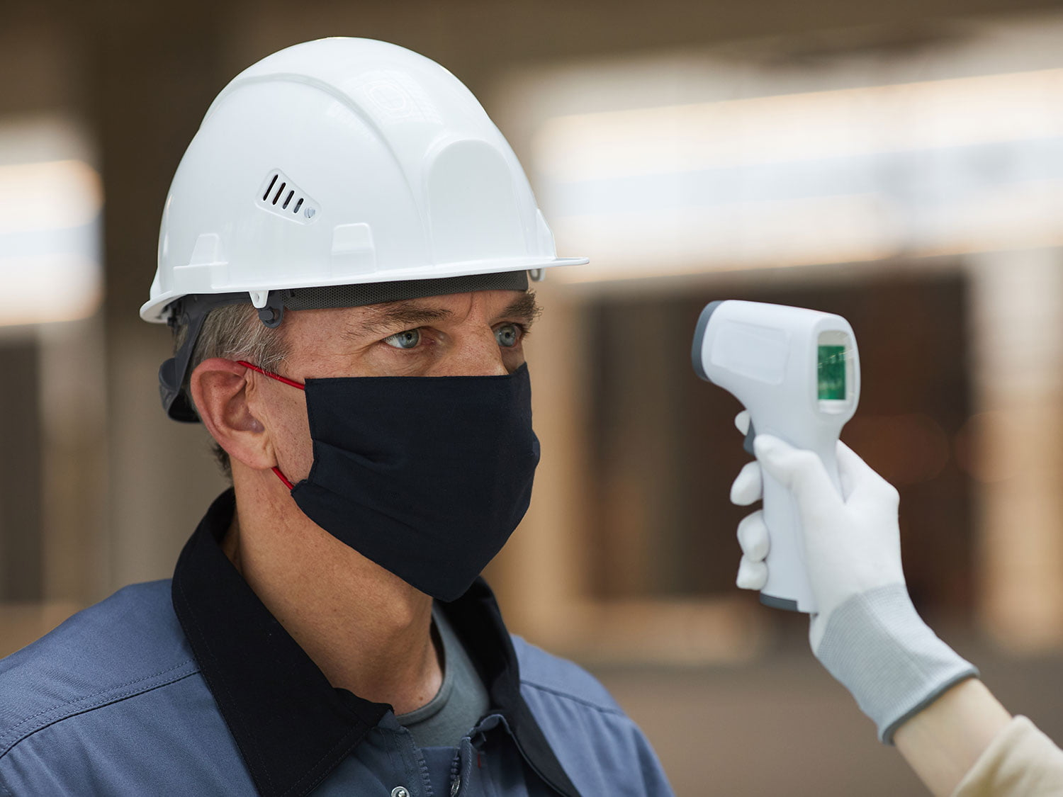 A construction worker gets a temperature check to test on-site for COVID-19