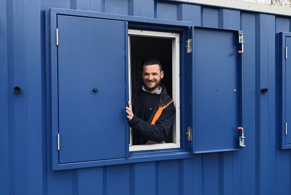 Smiling man in Philspace container window ready for work